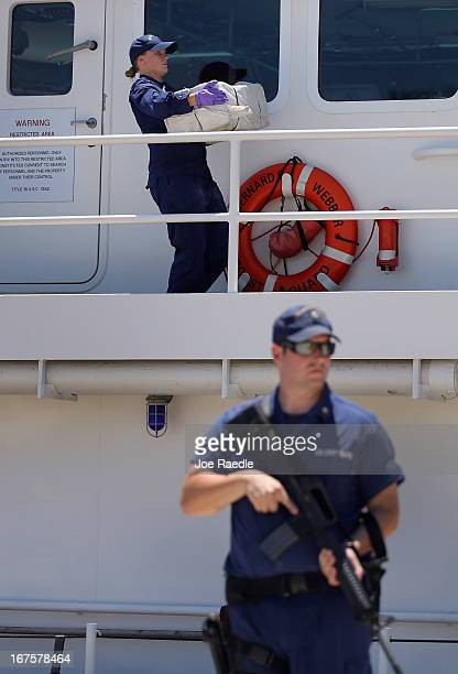 Under heavy security crew members from the Coast Guard Cutter Bernard C Webber off load some of the 2200 pounds of cocaine after it was seized during...