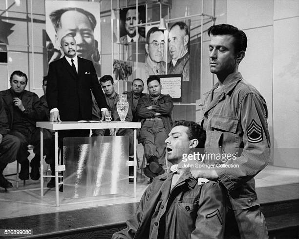 Under hypnosis a Brainwashed Harvey playing Raymond Shaw strangles a comrade at the instruction of the man at the table