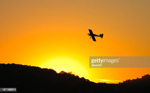 Under side of an airplane flying in an orange sky at sunset
