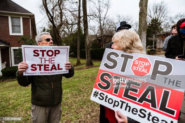 Under Siege protesters display their Stop The Steal signs in front Sen. Majority Leader Mitch McConnell's vandalized home on January 2, 2021 in...