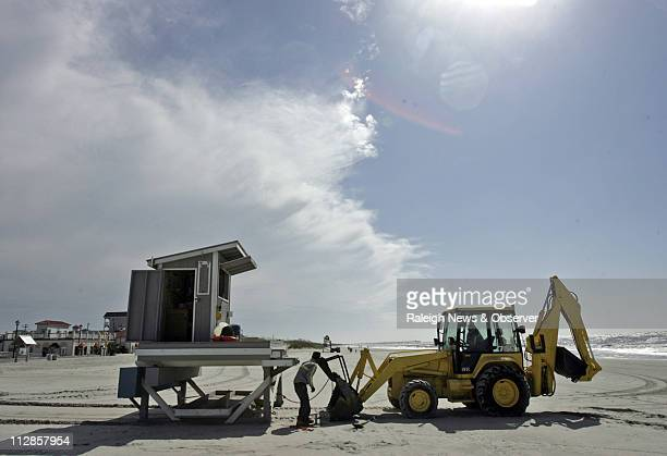 Under sunny blue skies workers use a backhoe to drag the lifeguard station back to its regular spot on Atlantic Beach North Carolina Friday September...