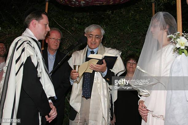 Under the Chuppa at an Orthodox Jewish wedding, a rabbi blesses the couple as the groom's parents look on, Jerusalem, Israel, May 27, 2005. The Rabbi...