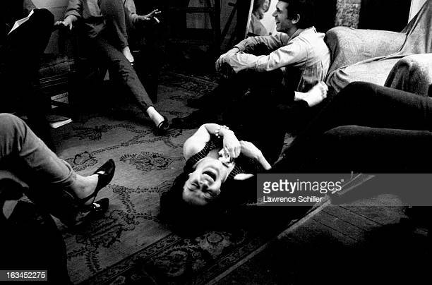 Under the influence of LSD a group of young people sit around a woman who rolls on the floor laughing San Francisco California 1966
