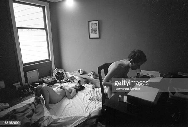Under the influence of LSD a naked young woman lies on a bed and a similarly naked young man works on a typewriter San Francisco California 1966