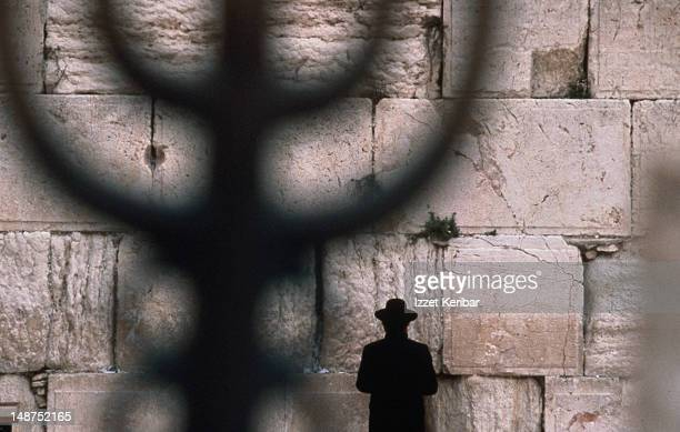 Under the shadow of the menorah, an orthodox Jew prays at the Western or Wailing Wall in the Old City of Jerusalem