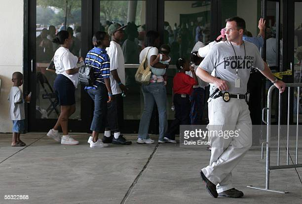 Under the watchful eye of a federal agent, evacuees line up to receive their FEMA debit cards at Reliant Arena, near the Astrodome September 9, 2005...
