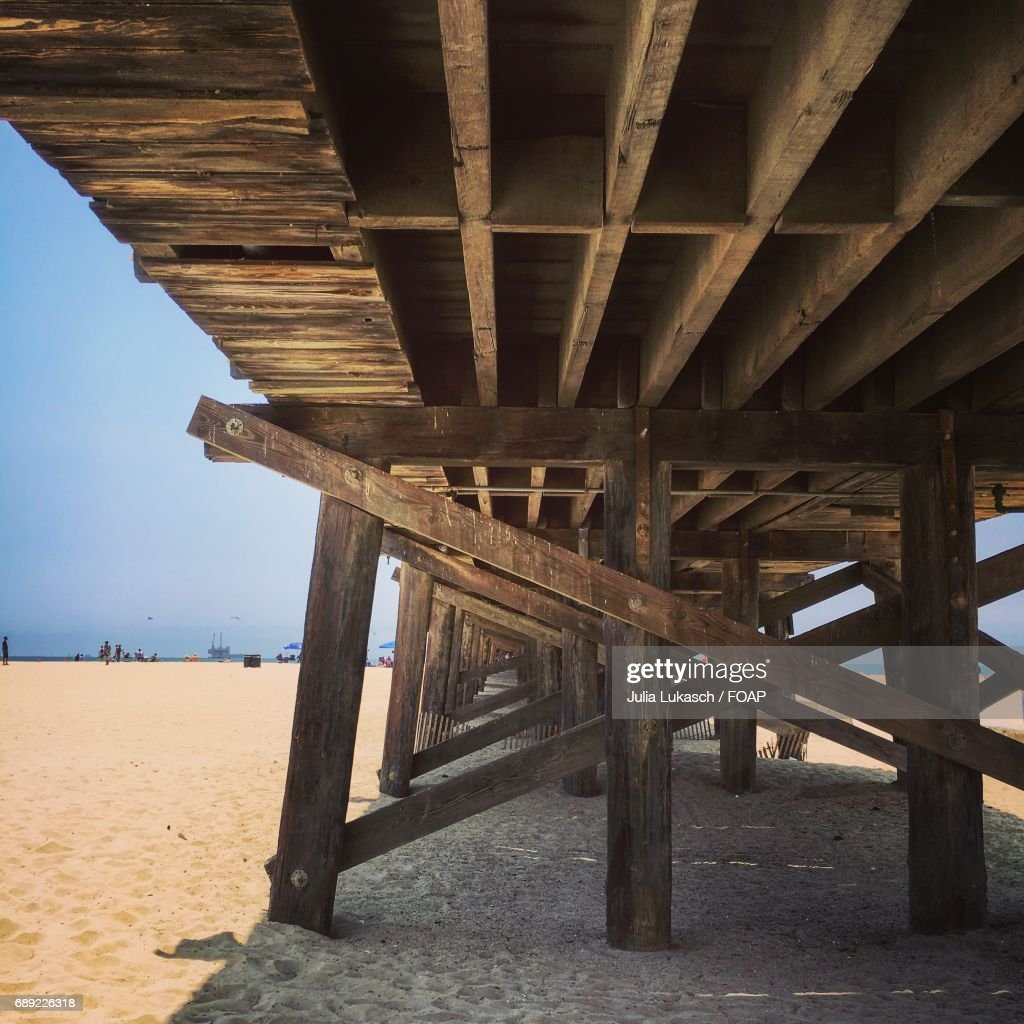Under view of wooden jetty at beach : Stock Photo