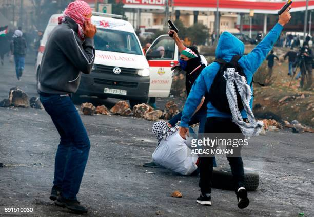 Undercover Israeli police detain a Palestinian protestor during clashes following a demonstration in the West Bank city of Ramallah on December 13 as...