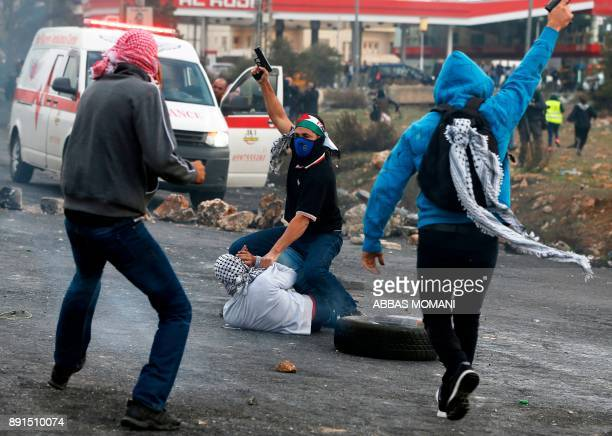 TOPSHOT Undercover Israeli police detain a Palestinian protestor during clashes following a demonstration in the West Bank city of Ramallah on...