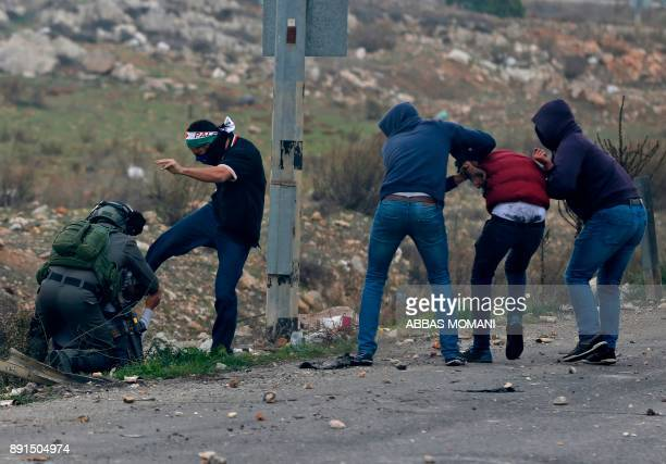 TOPSHOT Undercover police arrest Palestinian protestors stones throwers during clashes following a demonstration in the West Bank city of Ramallah on...