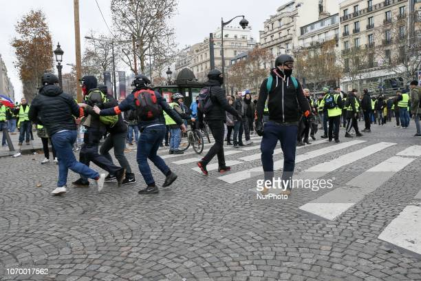 Undercover police officers arrest a protestor wearing a quotyellow vestquot on the Champs Elysees avenue during a demonstration against rising costs...