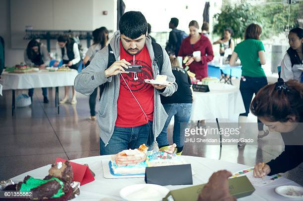 A undergraduate student taking a picture of a cake decorated for 'Life of Pi' by Yann Martel at the Edible Book Festival at Johns Hopkins University...