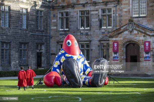 Undergraduate students at the University of St Andrews walk past Philip the Lobster in St Salvator's Quad, St Andrews.