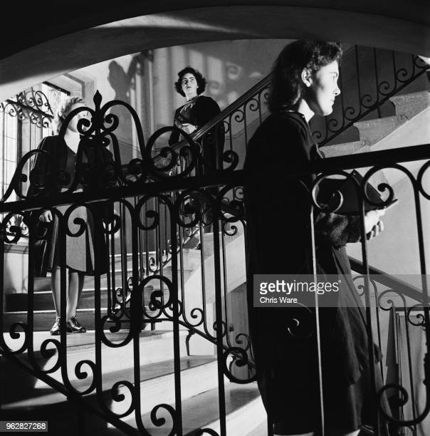 Undergraduate students descending the staircase from their rooms at Girton College, Cambridge, on their way to tutorials, October 1948. The women's...