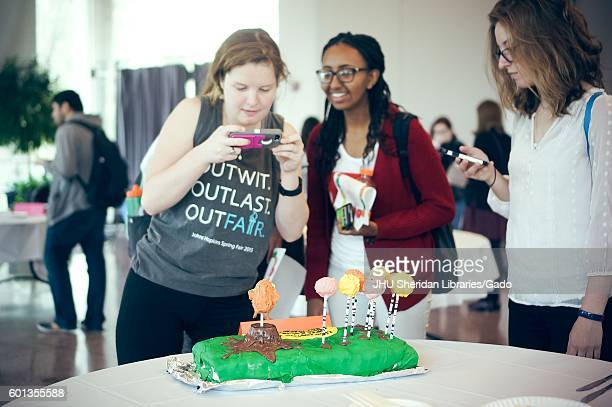 Undergraduate students taking pictures of a cake decorated for The Lorax at the Edible Book Festival at Johns Hopkins University Baltimore Maryland...