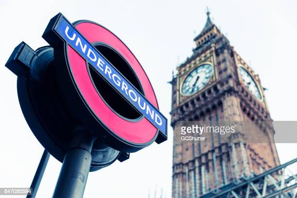 underground signage next to the world famous big ben. - underground sign stock pictures, royalty-free photos & images