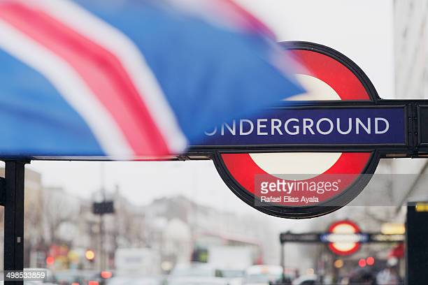 CONTENT] Underground subway sign typical in London Part of umbrella with Union Jack Flag colours in the foreground