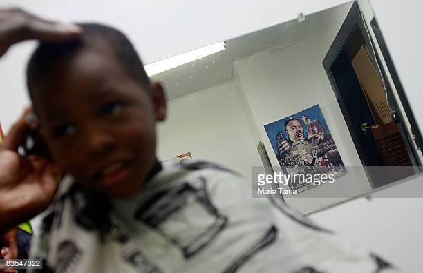 Underneath a poster featuring Martin Luther King Jr a boy gets his hair cut in a barber shop located in the Civil Rights District an area where...