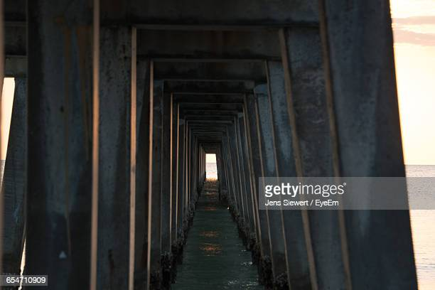 underneath view of pier at sea - jens siewert stock-fotos und bilder