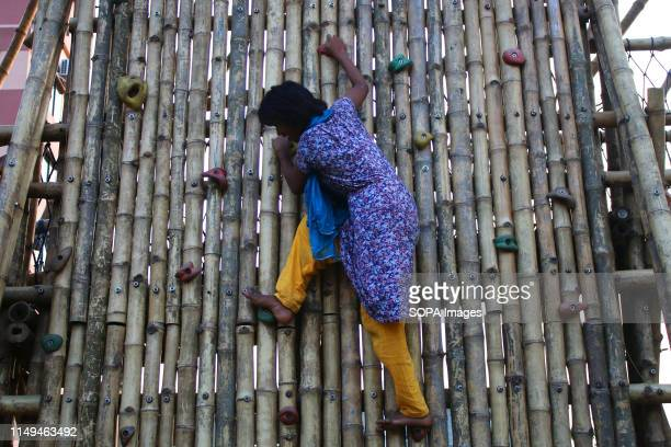 A underprivileged girl climbs a bamboo made wall inside the bamboo play space in Dhaka The unique play space built in Dhaka has brought smiles on the...