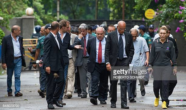 UnderSecretary for the Italian Ministry of Foreign Affairs Mario Giro and a group of Italian nationals walk away from the gate entrance near an...
