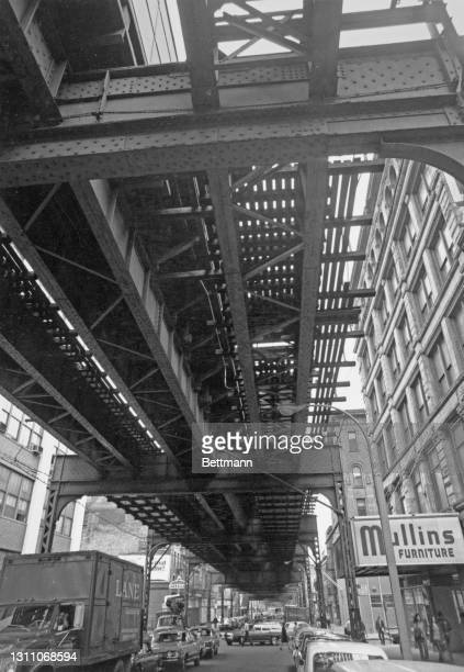 Underside view of the elevated rail line on Myrtle Avenue, with a sign for Mullins Furniture to the right of the image, in the Brooklyn borough of...