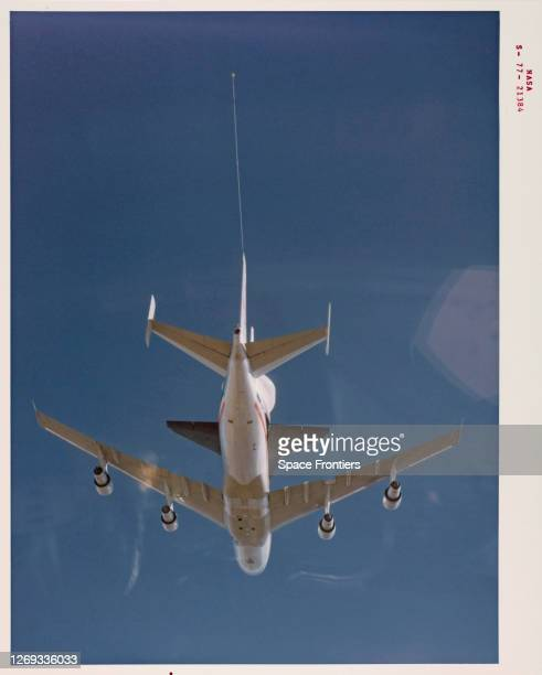 Underside view of the Space Shuttle Enterprise riding piggyback atop NASA 905, a 747 carrier aircraft, during the first of six Approach and Landing...