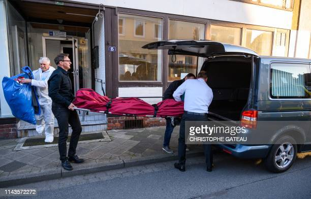 Undertaker carry a body bag on May 13 2019 out of a cordoned off house in Wittingen northern Germany where two bodies were found during...