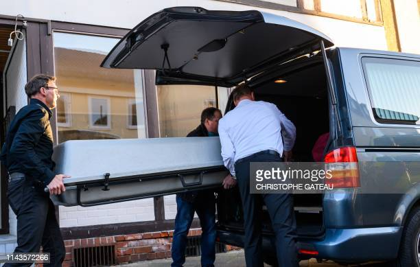 Undertaker carry coffin on May 13 2019 out of a cordoned off house in Wittingen northern Germany where two bodies were found during investigations...