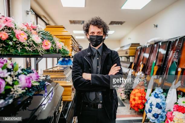 begrafenisondernemer in begrafenissalon met gezichtsmasker - uitvaartcentrum stockfoto's en -beelden