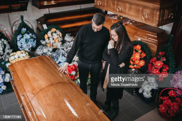 undertaker showing coffins and crosses to a widow - funeral stock pictures, royalty-free photos & images