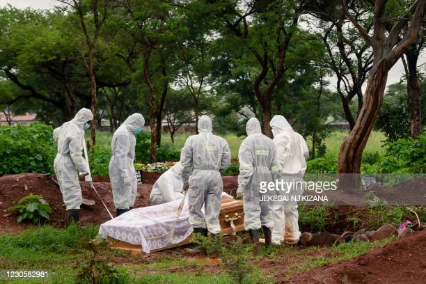 Undertakers in full body personal protective equipment lower the coffin of a person that passed away due to COVID-19 in to a grave at Glen Forest...