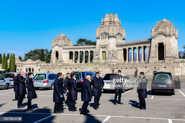 Undertakers wait by their hearse on March 16, 2020 on the parking lot of the Monumental cemetery of Bergamo, Lombardy, as burials of people who died...