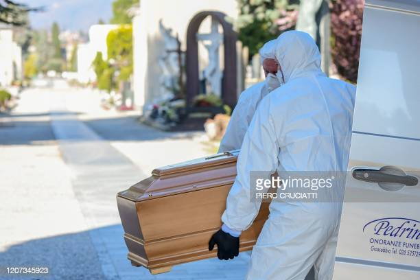 Undertakers wearing a face mask and overalls unload a coffin out of a hearse on March 16 2020 at the Monumental cemetery of Bergamo Lombardy as...
