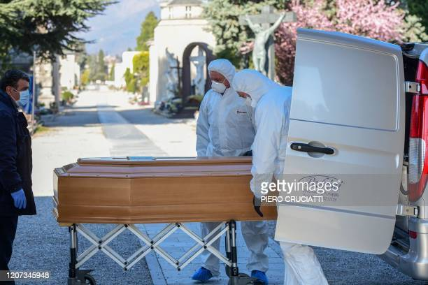 Undertakers wearing a face mask and overalls unload a coffin out of a hearse on March 16, 2020 at the Monumental cemetery of Bergamo, Lombardy, as...