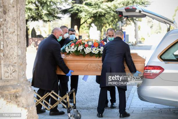Undertakers wearing a face mask carry a coffin out of a hearse on March 16 2020 at the Monumental cemetery of Bergamo Lombardy as burials of people...