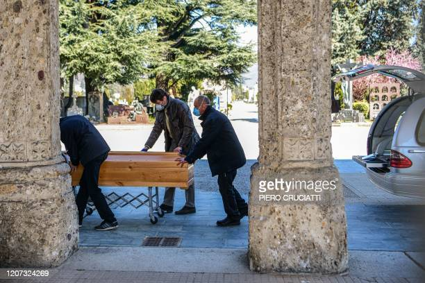 Undertakers wearing a face mask move a coffin out of a hearse on March 16 2020 at the Monumental cemetery of Bergamo Lombardy as burials of people...