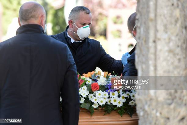 Undertakers wearing a face mask unload a coffin out of a hearse on March 16 2020 at the Monumental cemetery of Bergamo Lombardy as burials of people...