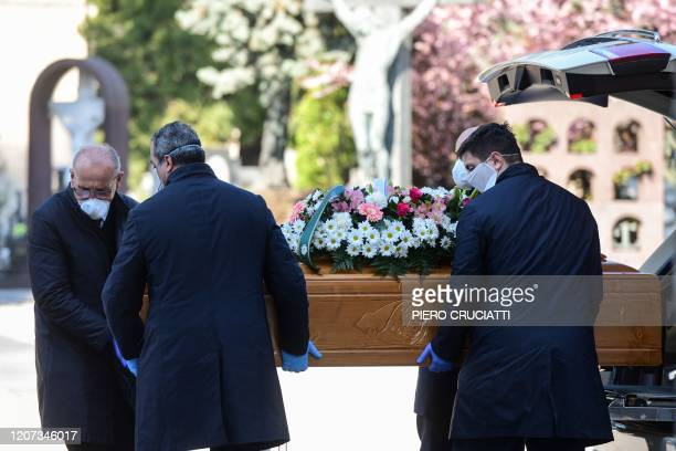 Undertakers wearing a face mask unload a coffin out of a hearse on March 16, 2020 at the Monumental cemetery of Bergamo, Lombardy, as burials of...