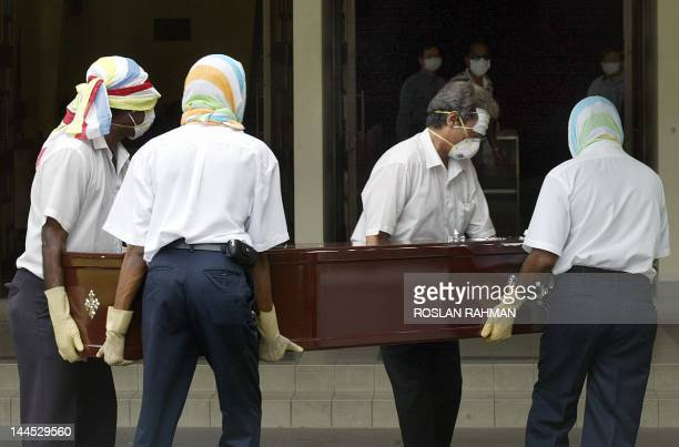 Undertakers with faces fully covered carry the coffin of the Singapore pastor who died of Severe Acute Respiratory Syndrome to be cremated in...