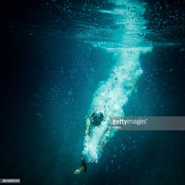 Underwater action shot of diver breaking water surface
