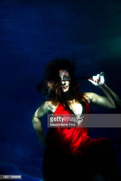 underwater circus. model posing underwater in the pool with hula hoop dressed in red and strong make-up. - alternative pose stock pictures, royalty-free photos & images
