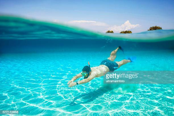 Underwater diving adventure  Young man snorkeling   Half-half  turquoise sea lagoon