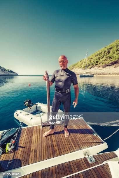 魚を捕まえた水中ハンター - 動物を使うスポーツ ストックフォトと画像