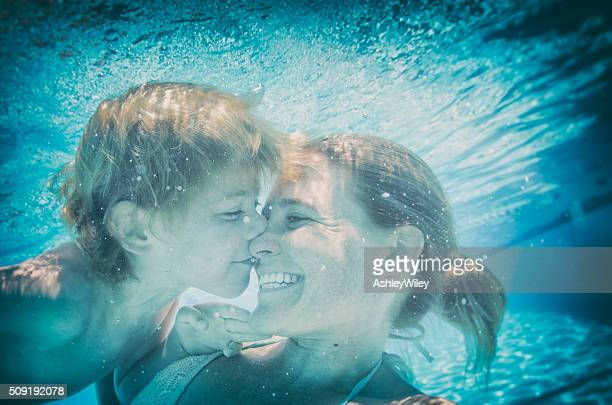 Underwater kisses selfie with mom and son in a pool