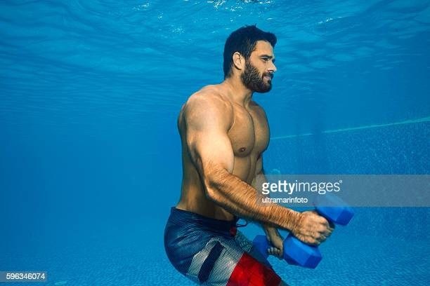 Underwater   Mid adult man training  with dumbbells  in swimming pool
