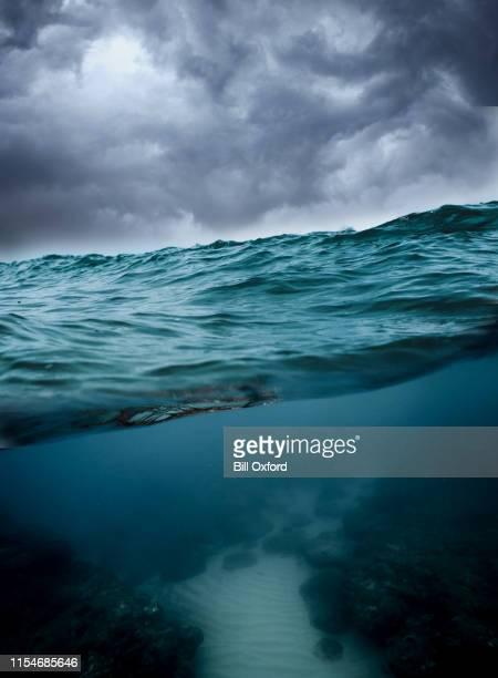 unterwasser, meer mit bewölktem himmel - wasseroberfläche stock-fotos und bilder