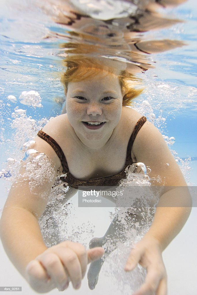 underwater photo of a female child as she swims in a pool : Foto de stock