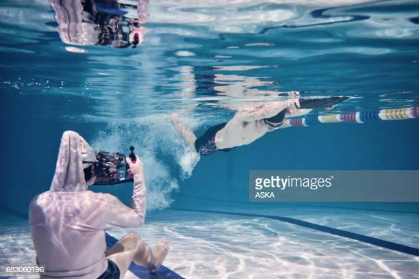 photographe sous-marin photographiant le nageur masculin dans une piscine - photographe professionnel photos et images de collection