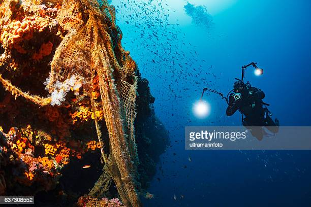 underwater photographer  scuba divers photographing  explore reef   old fishing net - cameraman stock photos and pictures